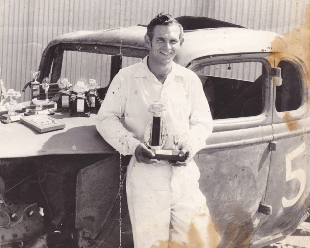Hank at 20 in the early 1950s with trophies won at Slauson Speedway.