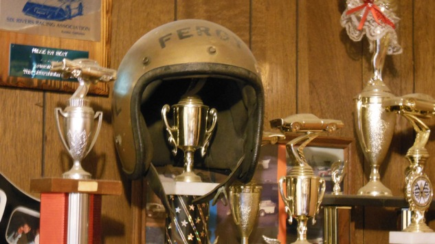 Among the trophies rests his first racing helmet, purchased for $14 in 1970.
