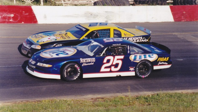 Angelo drives underneath Ronnie O'Neill in his 2002 Track Champion Miller Lite car