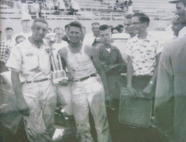 "On June 3, 1956, reigning NASCAR champ Herb Thomas joins Harold after they battled in a 200 lap race at the 1/2 dirt track at the Merced Fairgrounds.  ""I was changing the gears before the race so didn't have time to put on a shirt before getting in the car."""